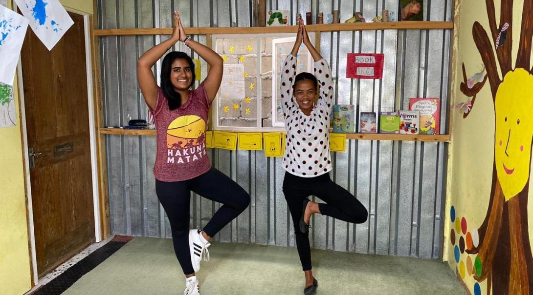 En volontär som åkt på en flexibel volontärresa lär ut yoga till en flicka i en kåkstad.